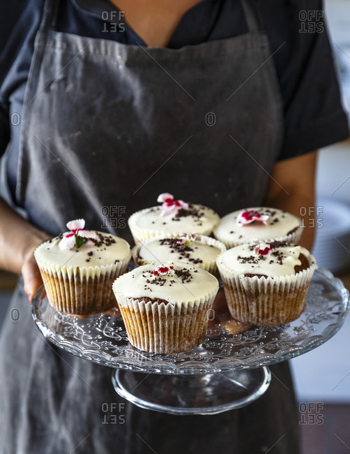Woman holding platter of cupcakes in Swedish café