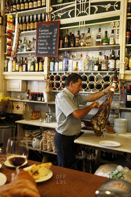 Andalucia, Spain -September 20, 2012: Man slicing meat at a tapas bar