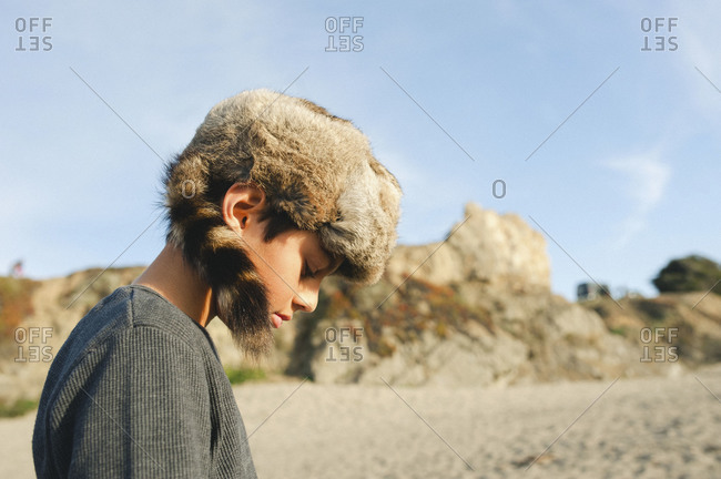 A boy on the beach wearing a raccoon tail hat