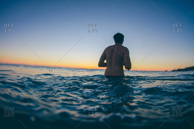 A man in the ocean at sunset