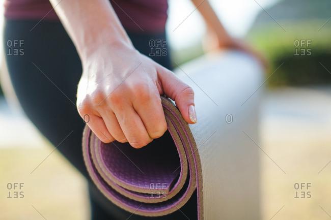 A woman unrolling a yoga mat