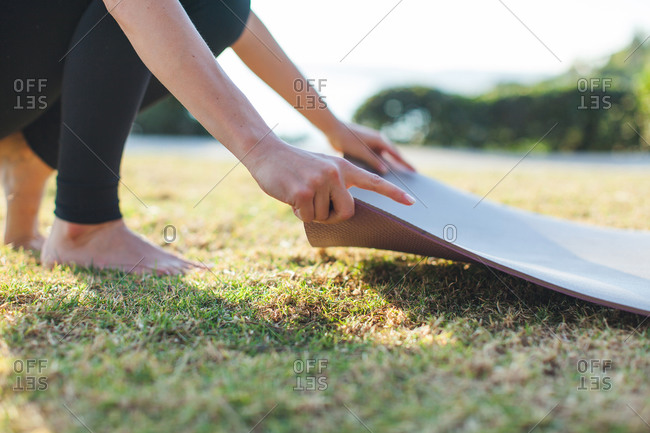 A woman lays down a yoga mat in the grass