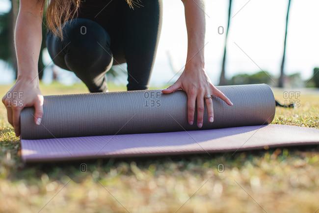 A woman rolls up a yoga mat