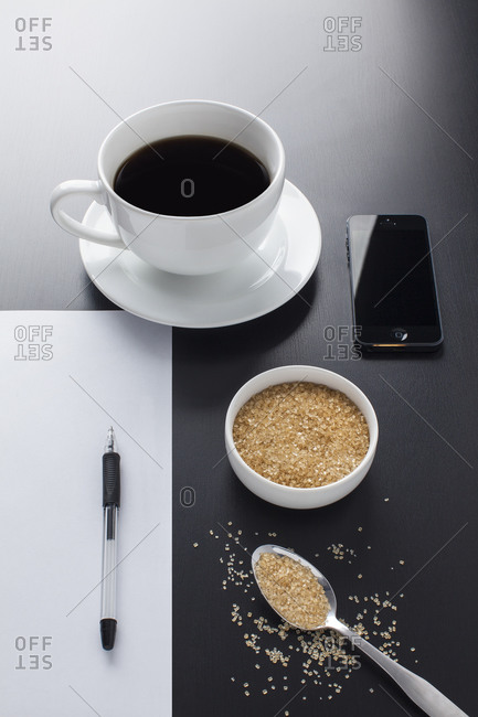 Coffee, sugar and mobile phone on dark table top