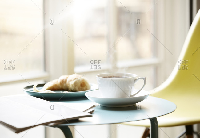 Morning coffee in a mug served with a croissant