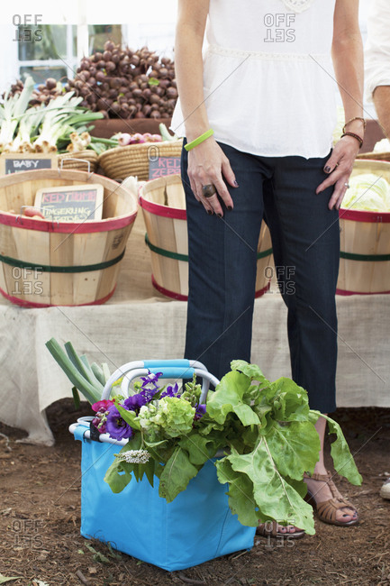 Woman standing next to purchases at farmer's market