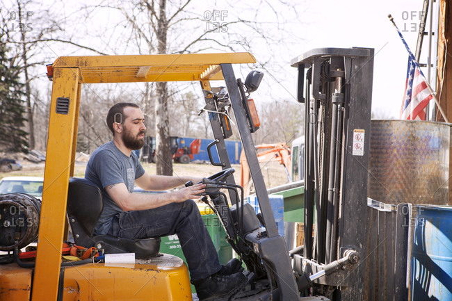 A man drives a forklift at a whiskey distillery