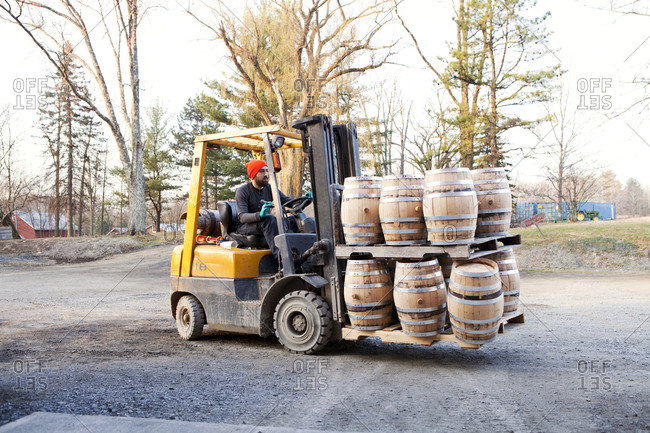 A distillery worker moving whiskey barrels