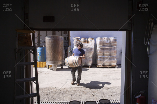 A man carries a barrel at a whiskey distillery