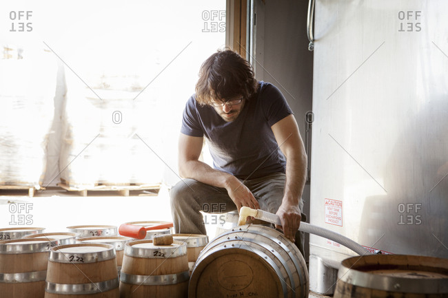 A man fills barrels with whiskey
