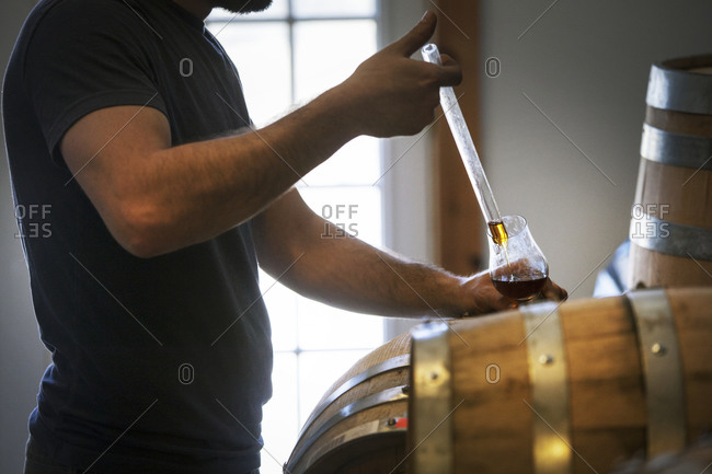 A man pours a glass of aged whiskey from a barrel