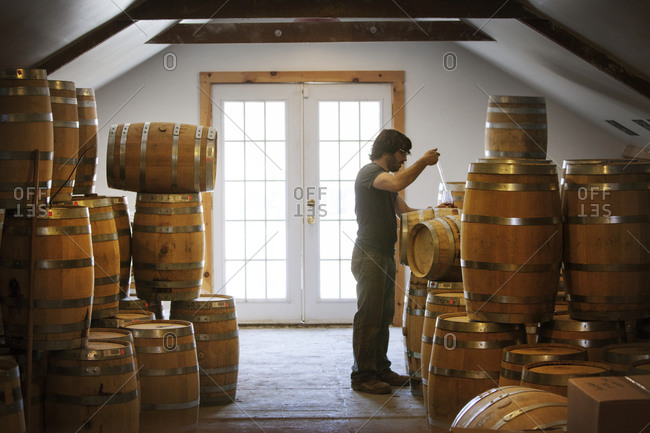 A man pours a glass of whiskey from a barrel