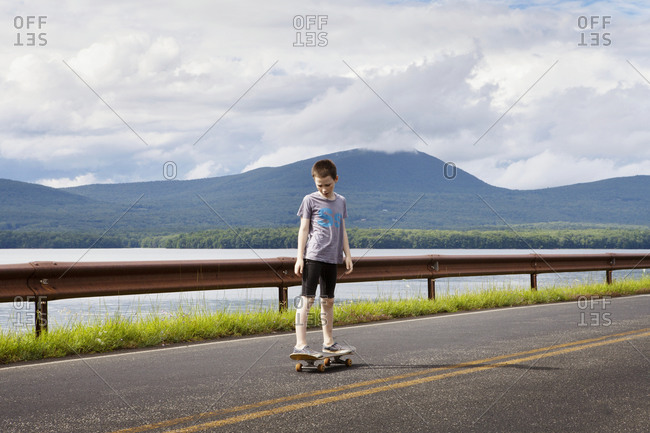 A young boy stands on a skateboard by a lake in the Catskills