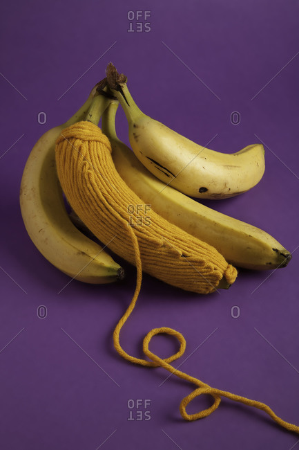 Yellow bananas with wool thread on a purple background