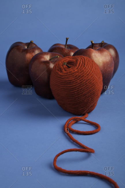 Red apples with wool thread on a blue background