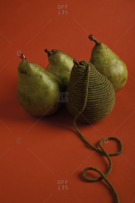 Pears with wool thread on a red background