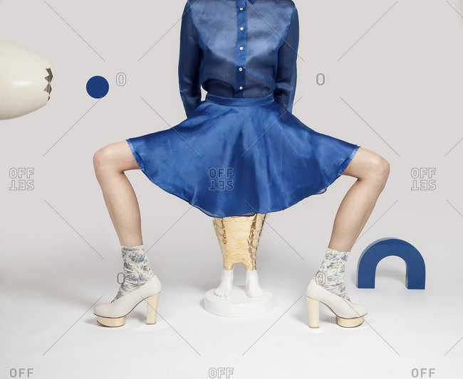 Woman in blouse, skirt and platform shoes with legs open