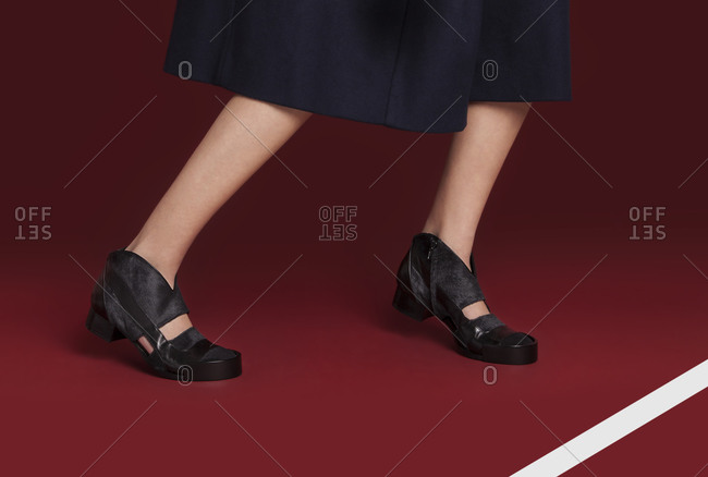Feet and legs of woman in conservative shoes and skirt