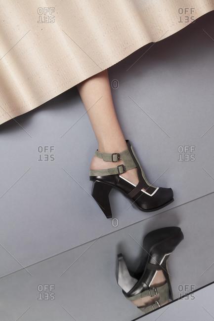 Woman's leg in high heels by mirror
