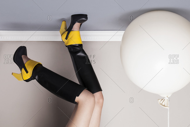 Woman in high heel boot with feet on ceiling