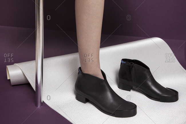 Feet and leg of woman with conservative shoes on rolled up mat