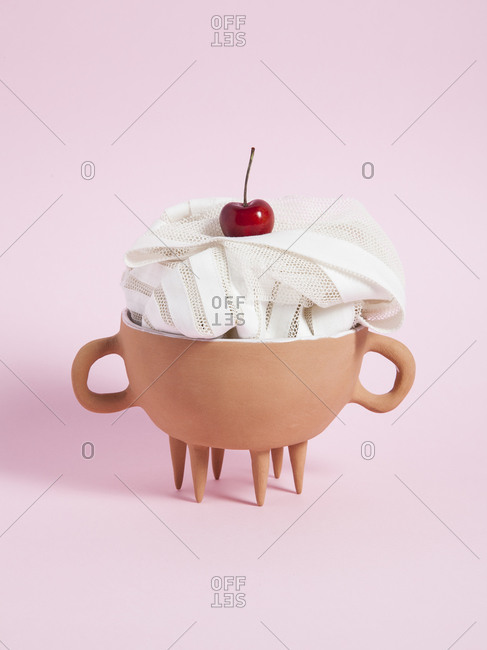 Material in bowl with cherry on pink background
