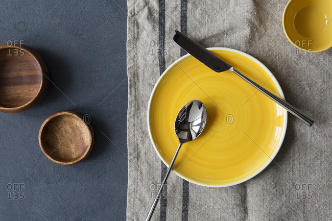Overhead view of wooden bowls and yellow dishes