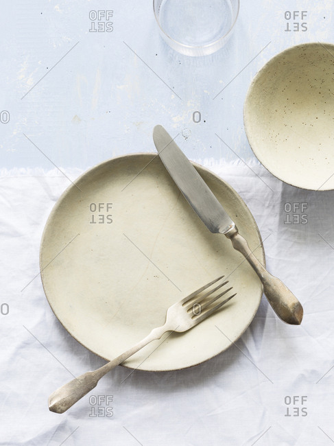 Rustic pottery dishes and flatware on marble surface