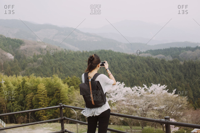 Young woman with backpack taking photo of a scenic view