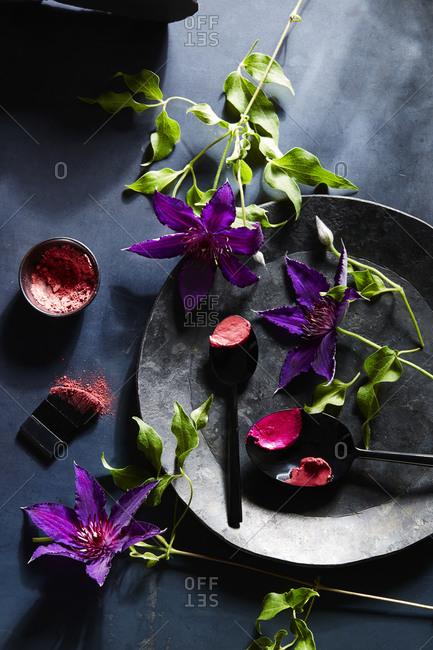 Purple flowers and makeup items arranged on dark gray slate surface