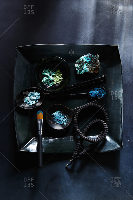 Blue-hued powdered eye shadows arranged on dish with rock and necklace