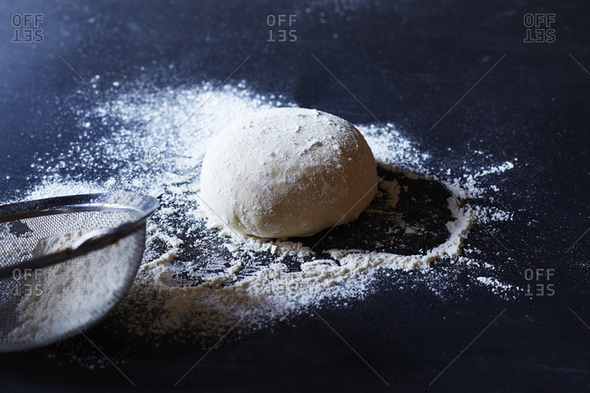 Ball of dough sprinkled with flour on counter