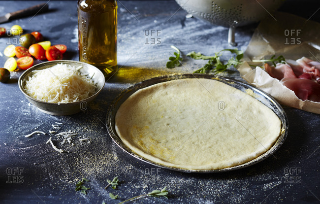 Pizza dough on a pan surrounded by ingredients