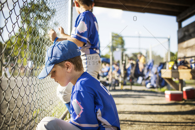 Youth league players wait in a dugout