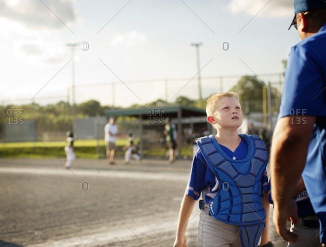 A youth league catcher talks with a coach