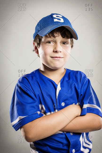 A youth leaguer stands with his arms crossed