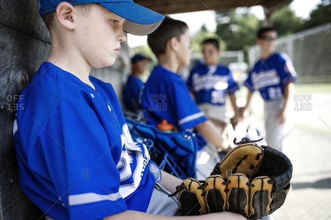 Boys wait in a baseball dugout