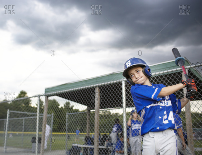 A youth league baseball player warms up on the sidelines