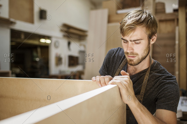 A carpenter lines up pieces of wood