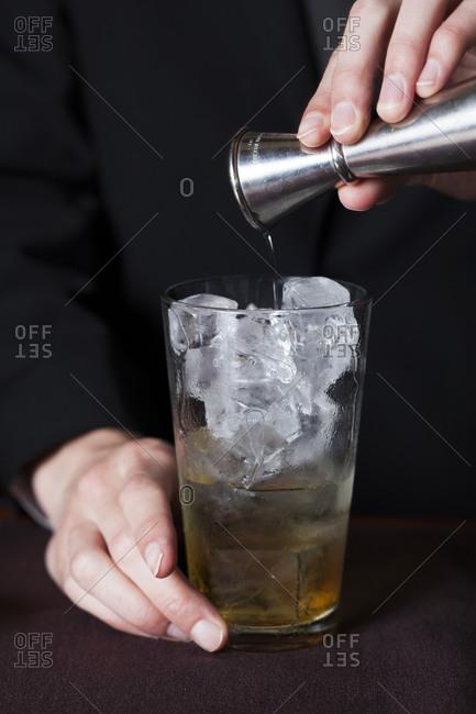 Bartender adding vodka to a cocktail