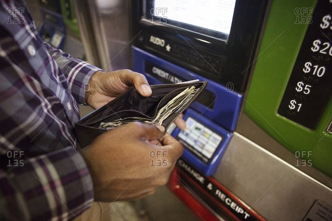 Man getting money out of wallet at transit card machine