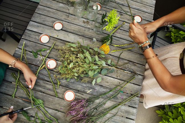 Overhead view of flowers being arranged on wooden table