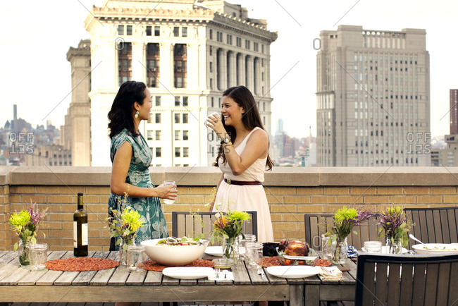 Two women at a rooftop dinner party