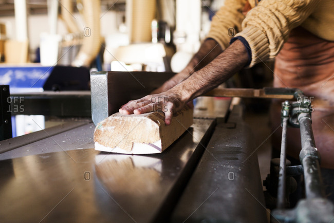 Close up of man cutting wood with a table saw