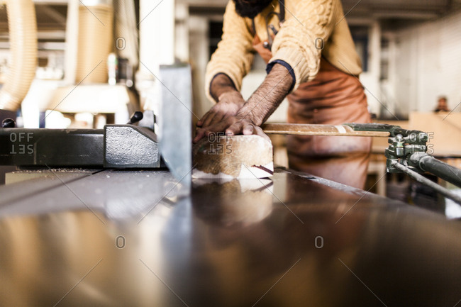 Man using a table saw to cut a piece of wood