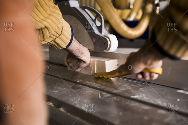 Man cutting a piece of wood on a table saw
