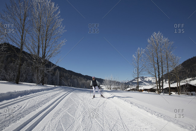 Woman cross country skiing through sunny rural trail
