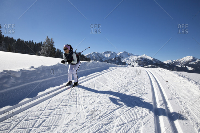 Woman coasting downhill while cross country skiing on rural trail
