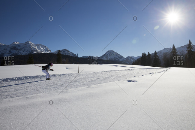 Woman coasting while cross country skiing on rural trail