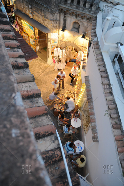 Positano, Italy - July 19, 2011: A sidewalk cafe and street vendors